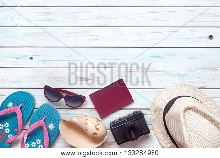 Travel summer background with objects inluding sunglasses passport and camera over a wooden background with space