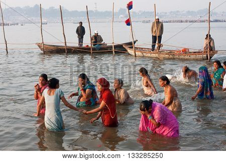 ALLAHABAD, INDIA - JAN 27, 2013: Young women swim in sacred water of Sangam at early morning on the festival Kumbh Mela on January 27, 2013 in India. Kumbh Mela 2013 had take 130 000000 visitors
