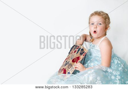 caucasian curly blond surprised girl in a ball gown in the New Year with Christmas snowflakes Christmas gift bags of brown paper in a pattern mittens christmas tree Christmas gifts in hands on isolated white background studio