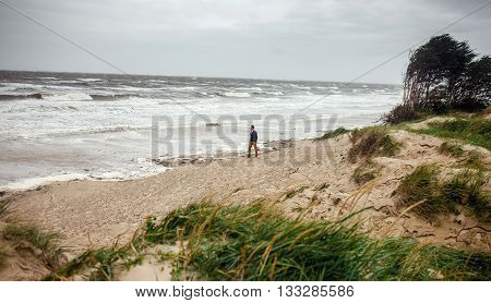 Picture of alone man walking on a beach in summer storm. Concept of loneliness, bad weather