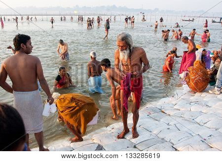 SANGAM, INDIA - JANUARY 27, 2013: Senior asian man come out from water in the confluence of the Ganges and the Yamuna during the biggest festival on Earth Kumbh Mela on January 27, 2013 in India