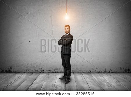 Smiling businessman looking at the camera with glowing bulb over his head. Symbol of ideas. Inspiration. Good idea worth its weight in gold. Good idea is the way to wealth and success. Targeting success and happiness. Afflatus.