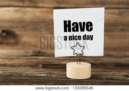 White note paper on a holder on brown wooden background, have a nice day