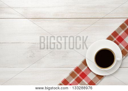Office workplace with cup of coffee on checkered tablecloth. Top view composition. Improving mood and productivity. Increasing productivity in the mornings. Willingness to work overtime. Keeping healthy. Contribution to wellbeing. Reducing stress. Workpla
