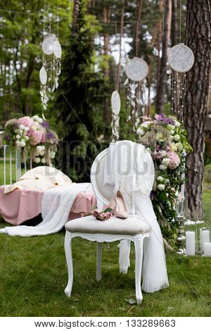 Beautiful wedding shoes with high heels and a bouquet of colorful flowers on a vintage chair on the nature in sunset light decorations preparing for the wedding details boudoir