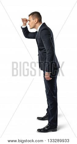 Side view of businessman standing and looks into the distance, isolated on white background. Successful lifestyle. Business staff. Office clothes. Dress code. Presentable appearance. Self-confidence.