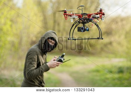 Man in mask operating a drone with remote control.