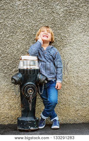 Vertical portrait of adorable little boy of 4-5 years old, having fun outdoors, playing with black hydrant