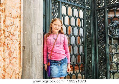 Outdoor portrait of fashion little girl of 7-8 years old, wearing denim skirt, purple bag