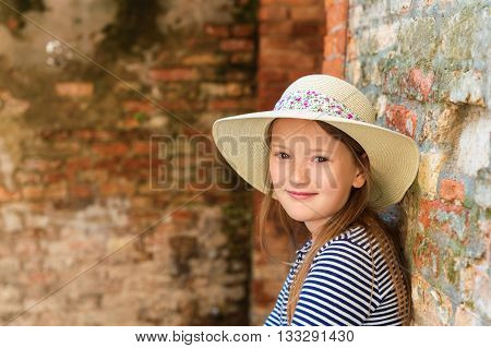 Outdoor close up portrait of pretty little girl of 8-9 years old, wearing hat, standing against old brick wall