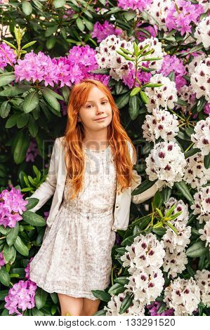 Spring portrait of adorable little redheaded girl of 8-9 years old, wearing white dress and jacket, playing in garden