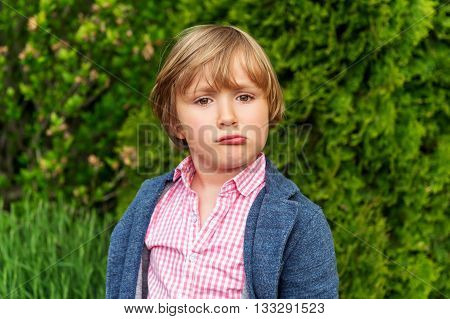Outdoor portrait of cute and sad little boy
