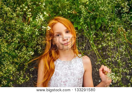 Close up outdoor portrait of adorable little girl of 8-9 years old . Red hair sweet young girl of 7-8 years old.