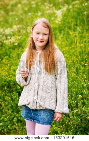 Outdoor portrait of adorable little girl of 8-9 years old, wearing beige knitted jacket, posing in green field