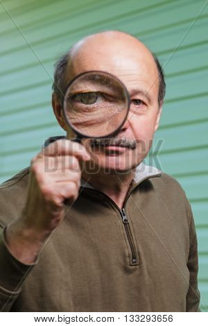 elderly man with a mustache holding a magnifying glass. Big eye through a magnifying glass