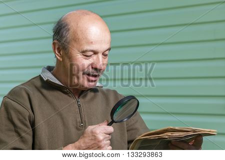 Pensioner Reads Ad In The Newspaper, Looking Through A Magnifying Glass. Vision Problems In Old Age