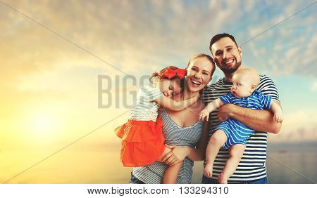 happy family of father mother and two children baby son and daughter on the beach at sunset
