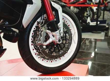 The front wheel of a motorcycle. Close up brakes and spokes