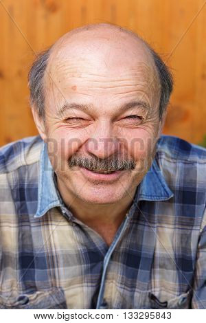 older man squinting from the sun. Good mood during the holidays