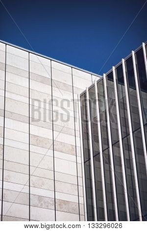 Low Angle Architectural Detail of Modern Office Building with Tile and Glass Facade on Sunny Day with Clear Blue Sky