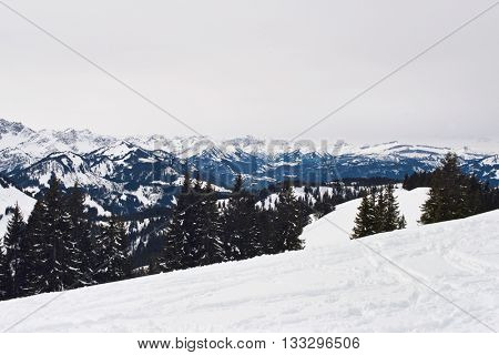 View from atop ski hill of cloudy skies above vast snow covered mountain range and scattered evergreen forests in the background