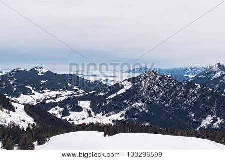 View from atop ski hill of cloudy skies above vast snow covered mountain range and scattered evergreen forests