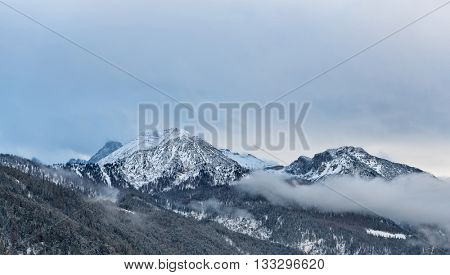 View of Alps mountain peaks and slow moving thick clouds around them with foothills in foreground during winter season