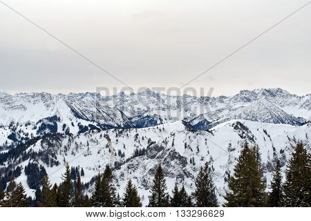 Panoramic scene of snow-covered alpine mountain peaks looking across the top of a pine forest to rugged mountains and valleys