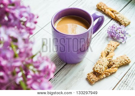 Cup of coffee biscuits and bouquet of purple lilac spring flowers on rustic wooden background