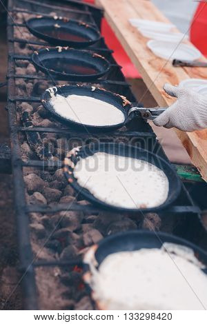 Pancakes are fried on coals in a cast iron skillet