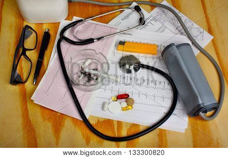 Cigarette In The Ashtray And Stethoscope, Blood Pressure Monitor, Pills