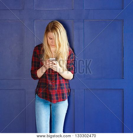 Pretty Woman Calling Someone Through Mobile Phone While Smiling at the Camera Against Blue Wall Background