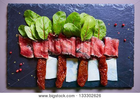 slices of ham with cheese and leaves of beets on the plate