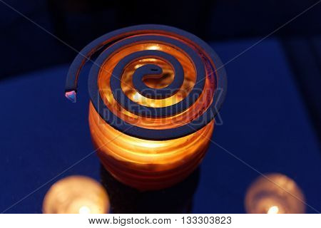 Lit Mosquito Coil and Citronella Candle in Evening Light, to Deter Mosquitoes, Flies and Midgies