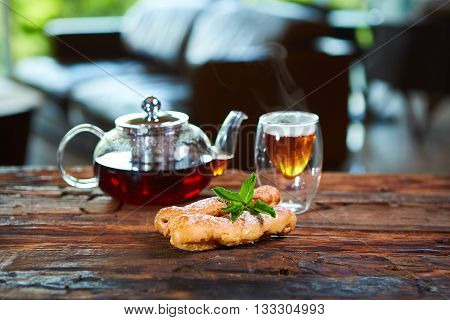 Tasty eclair and cup of tea and teapot on wooden table