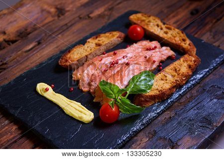 salmon slices and tomatoes on black plate