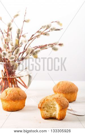 Branches of a willow and biscuits on a light background. A willow in a transparent glass vase one biscuit is taken a bite on a white wooden table the fork lies