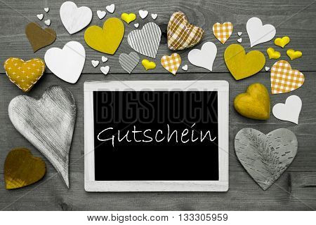 Chalkboard With German Text Gutschein Means Voucher. Many Yellow Textile Hearts. Grey Wooden Background With Vintage, Rustic Or Retro Style. Black And White Style With Colored Hot Spots