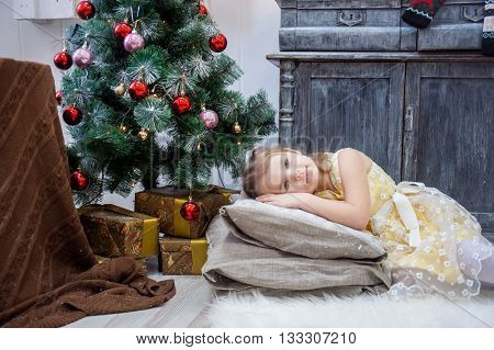 little girl lies on pillows in a yellow dress Christmas