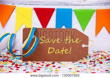 Label With English Text Save The Date. Party Decoration Like Streamer, Confetti And Bunting Flags. White Wooden Background With Vintage, Retro Or Rustic Syle
