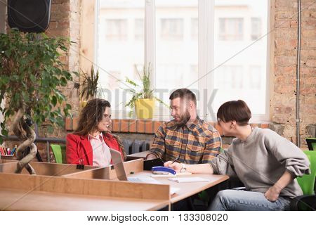 Picture of business people sitting at working places and working in office. Happy people discussing business problems and issues.
