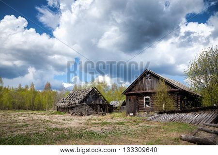Old abandoned log house and barn in a desolated village