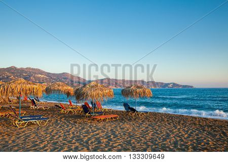 Red and blue sun loungers with parasols on a beach in evening light
