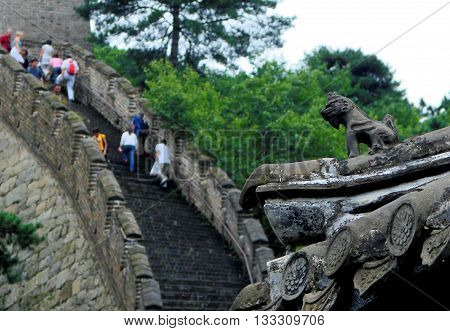 Dragon Gargoyle on Great Wall of China Guard Tower Watches over Tourists Climbing a Steep Section of Wall near Mutianyu outside Beijing
