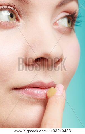 Female putting applying lip balm moisturizing balsam. Girl taking care of lips. Skincare.