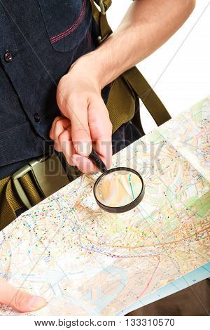 Tourist backpacker reading map with magnifying glass loupe. Hiker searching looking for direction guide. Summer vacation travel. Isolated on white background.