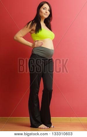 Happiness and motherhood concept. Pregnant fit woman in sportwear on red background