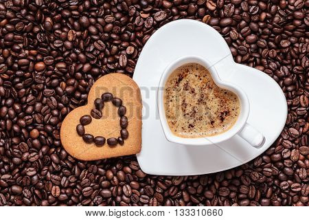 Coffee time concept. Heart shaped cup with cappuccino mocha and cookie gingerbread on coffee beans background. Top view