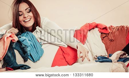 Woman Behind Sofa Full Of Clothes With Stretched Arm.