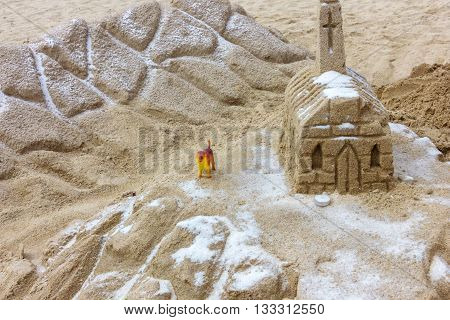 Small castle built of sand on beach is guarding of toy dog